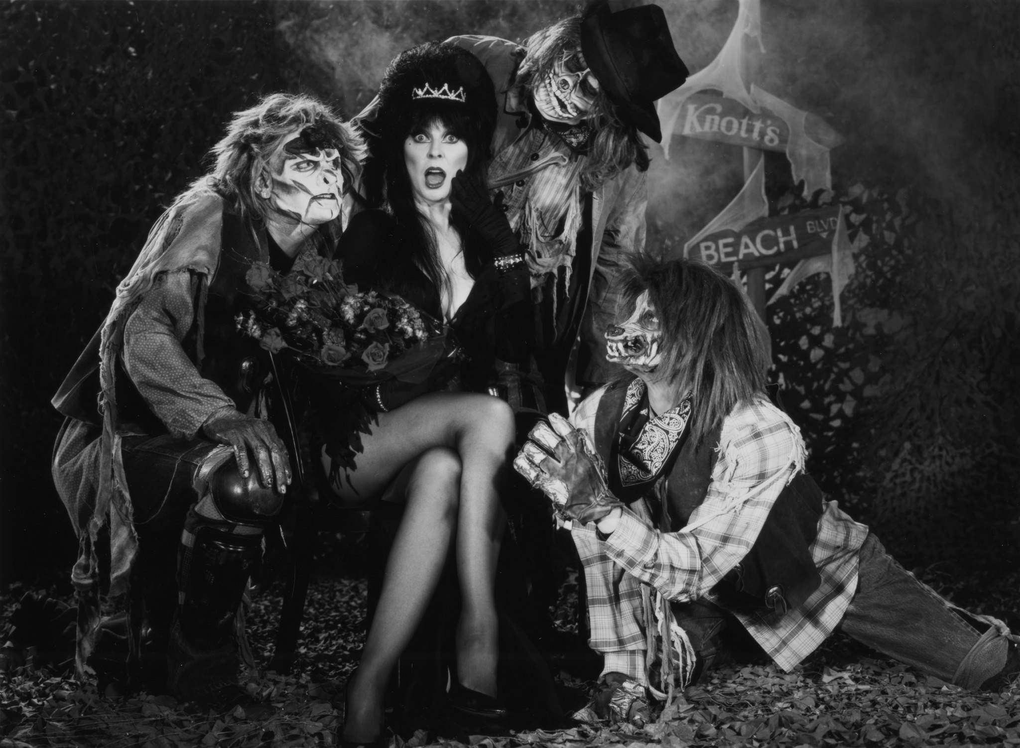"""Elvira, the """"horror hostess,"""" sits with some zombies at Knott's Berry Farm."""